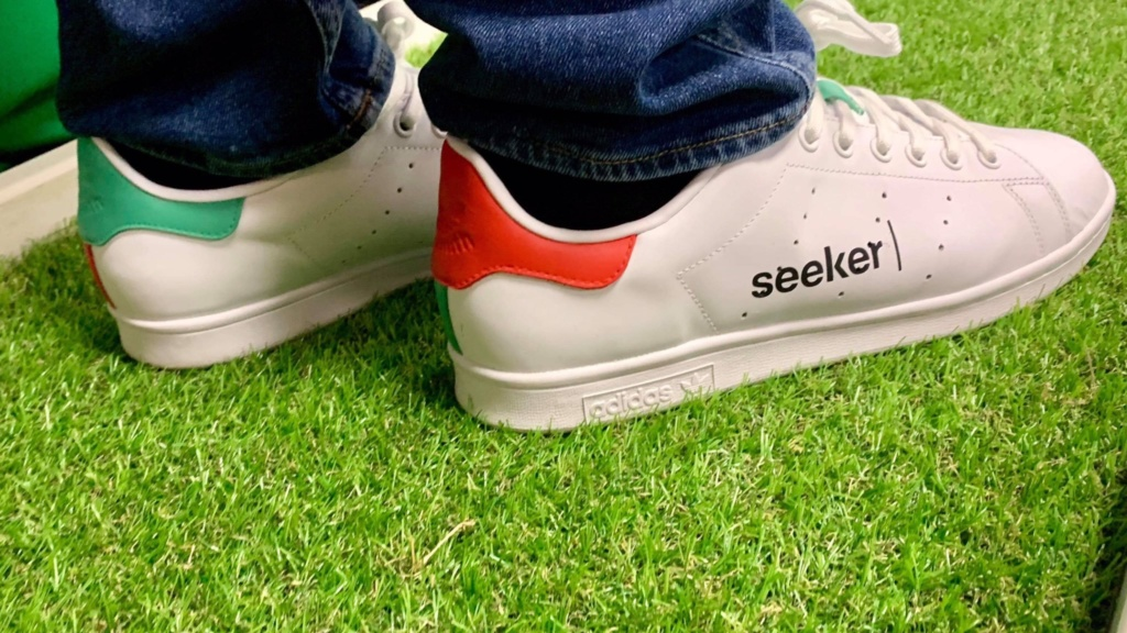 A pair of white, orange, and green sneakers